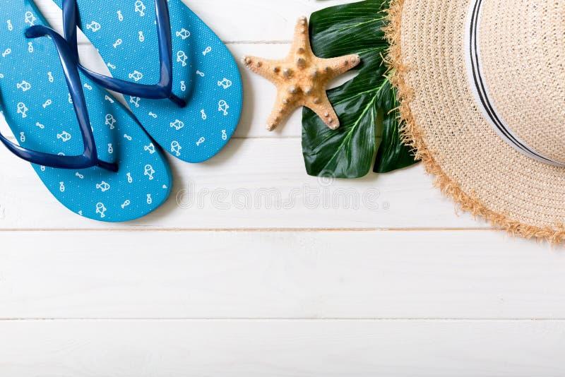 Chapeau de paille, feuille verte, bascules électroniques bleues et étoiles de mer sur un fond en bois blanc concept de vacances d image libre de droits