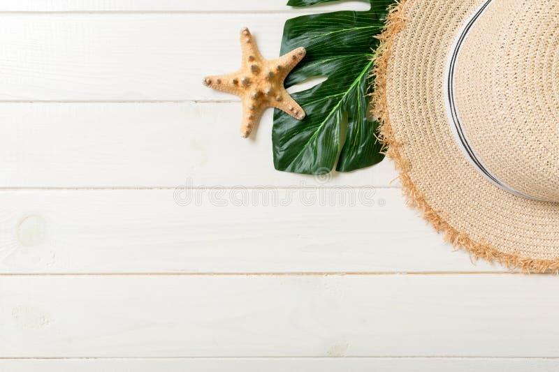 Chapeau de paille, feuille verte et étoiles de mer sur un fond en bois blanc concept de vacances d'?t? de vue sup?rieure avec l'e photos stock