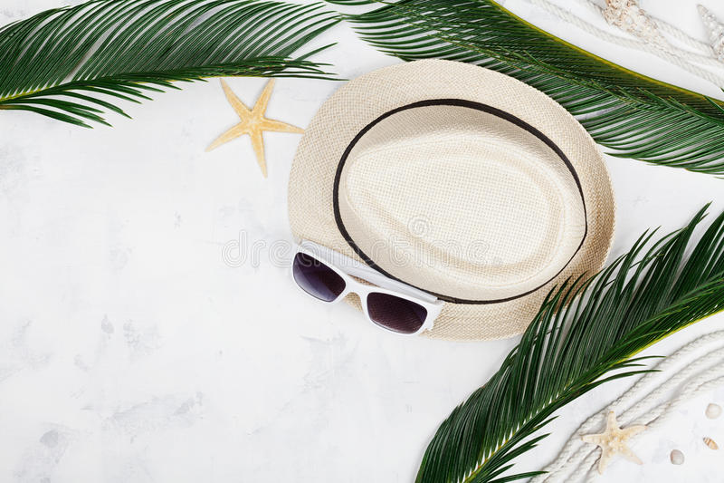 Chapeau de paille, lunettes de soleil, palmettes, corde, coquillage, étoile de mer sur la vue supérieure de table, configuration  photo libre de droits