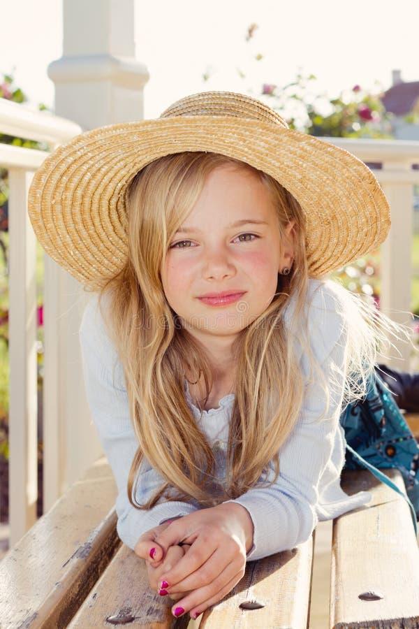 Chapeau de paille s'usant de fille dans le jardin image stock