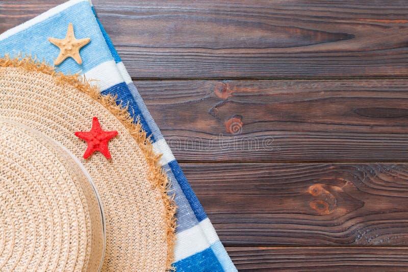 Chapeau de paille, serviette bleue et ?toiles de mer sur un fond en bois fonc? concept de vacances d'?t? de vue sup?rieure avec l photo stock