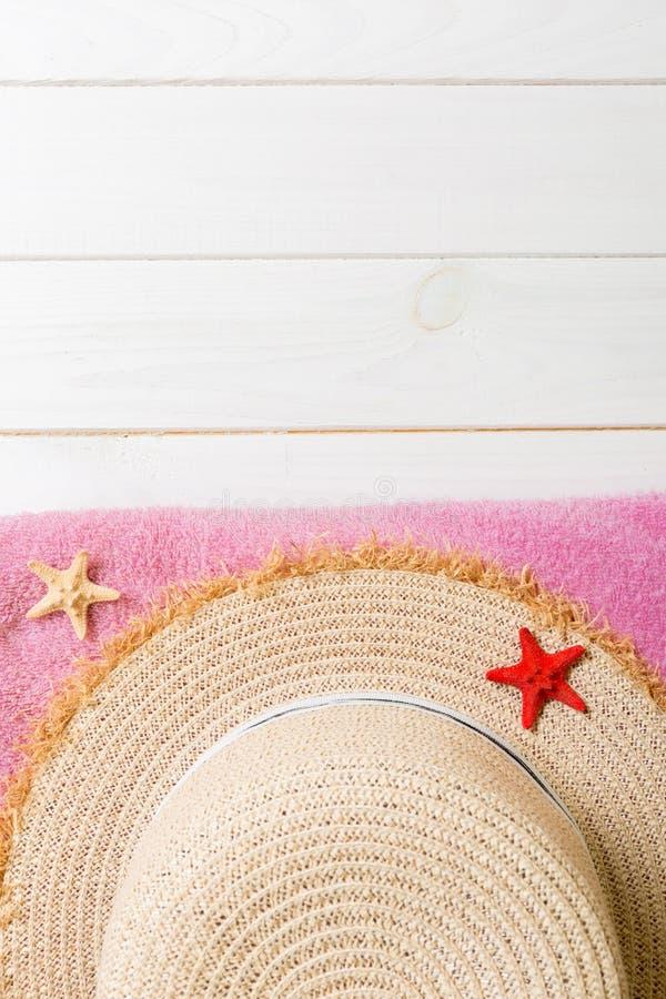 Chapeau de paille, serviette rose et étoiles de mer sur un fond en bois foncé concept de vacances d'?t? de vue sup?rieure avec l' photo stock