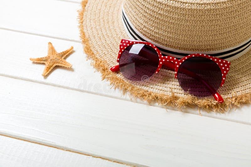 Chapeau de paille, verres de soleil et coquillages sur un fond en bois blanc concept de vacances d'?t? de vue sup?rieure avec l'e image libre de droits