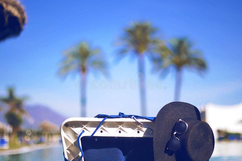 Chapeau de paille, verres de soleil sur le canapé, près de la piscine photographie stock
