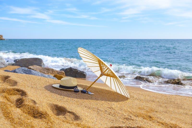 Chapeau de Panama et parapluie de plage sur la plage sablonneuse près de la mer Vacances d'été et concept de vacances pour le tou image stock