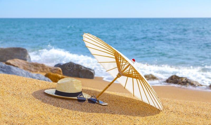 Chapeau de Panama et parapluie de plage sur la plage sablonneuse près de la mer Vacances d'été et concept de vacances pour le tou photo stock