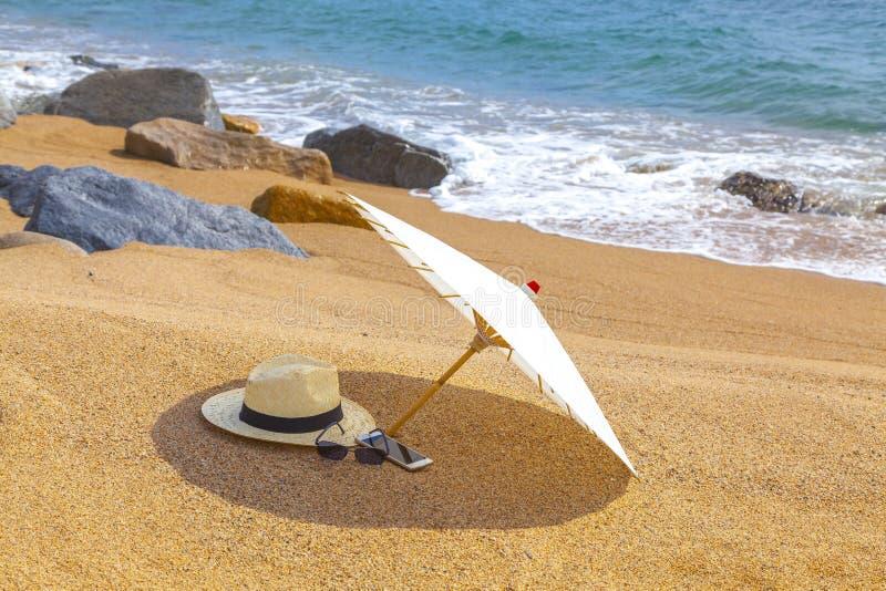 Chapeau de Panama et parapluie de plage sur la plage sablonneuse près de la mer Vacances d'été et concept de vacances pour le tou photos stock