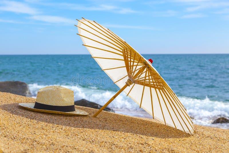 Chapeau de Panama et parapluie de plage sur la plage sablonneuse près de la mer Vacances d'été et concept de vacances pour le tou image libre de droits