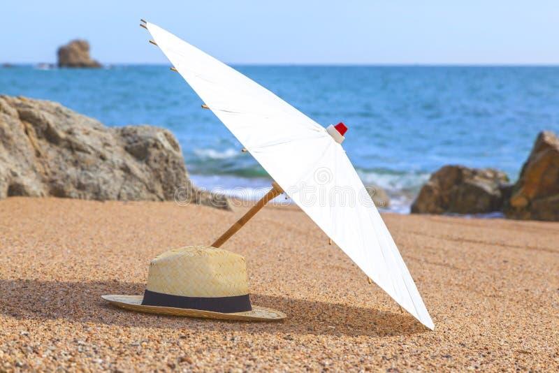 Chapeau de Panama et parapluie de plage sur la plage sablonneuse près de la mer Vacances d'été et concept de vacances pour le tou photographie stock libre de droits