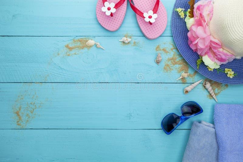 Chapeau de plage de dame d'été, chaussures de plage avec le coquillage, lunettes de soleil et sable sur le fond en bois bleu, con photo stock