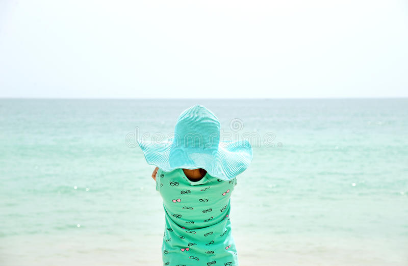 Chapeau de port adorable de petite fille se tenant à la plage pendant des vacances d'été photographie stock libre de droits