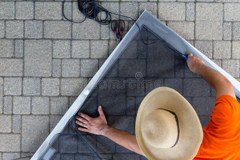 Chapeau de port d'homme réparant la vieille porte de patio photo stock
