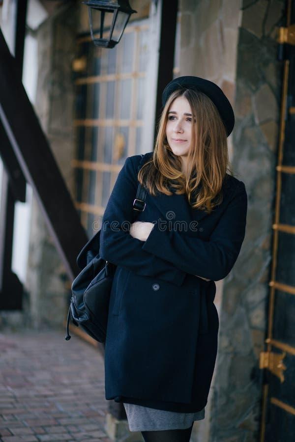 Chapeau de port de belle jeune femme et manteau bleu-foncé marchant sur une rue de ville photographie stock libre de droits