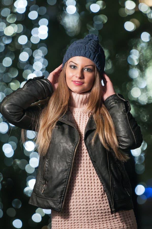 Chapeau de port de dame à la mode et veste noire extérieurs dans le paysage de Noël avec les lumières bleues à l'arrière-plan. Por image libre de droits