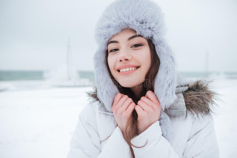 Chapeau de port de jeune femme gaie au jour d'hiver froid images stock