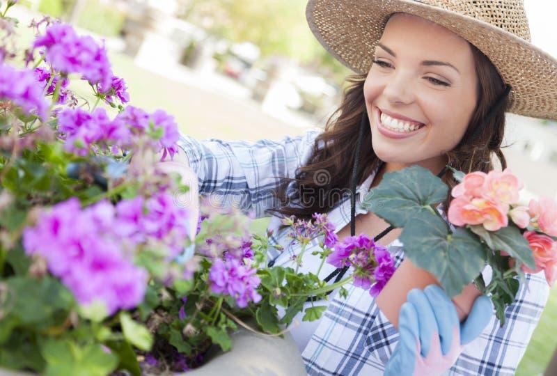 Chapeau de port de sourire de jeune femme faisant du jardinage dehors photographie stock