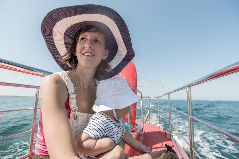 Chapeau de port de femme se reposant avec l'enfant sur la plate-forme de bateau photo stock