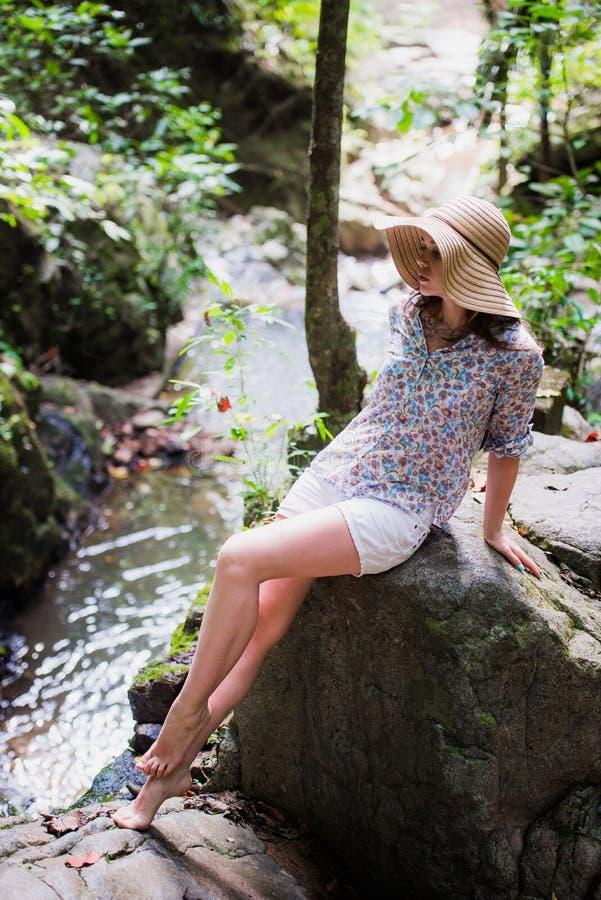 Chapeau de port de fille élégante de voyageur et regarder la rivière dans des vacances d'été ensoleillées de forêt concept de voy photos stock