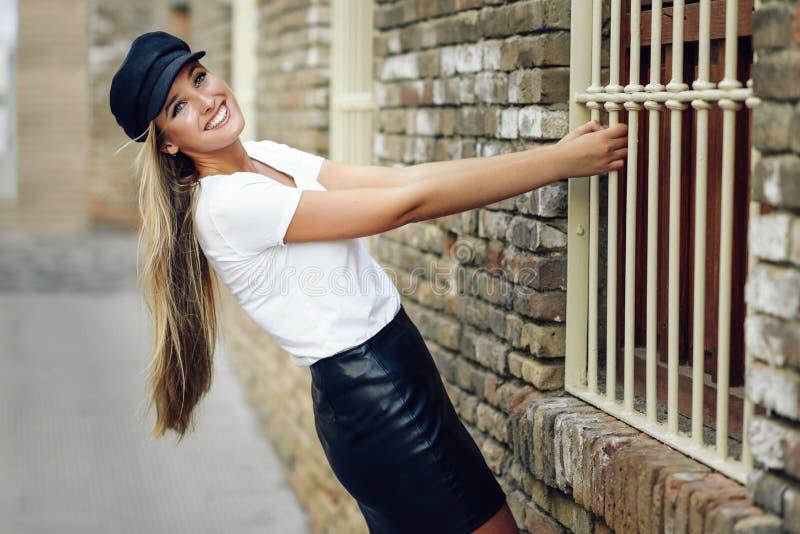 Chapeau de port de jeune femme blonde souriant près d'un mur de briques photographie stock