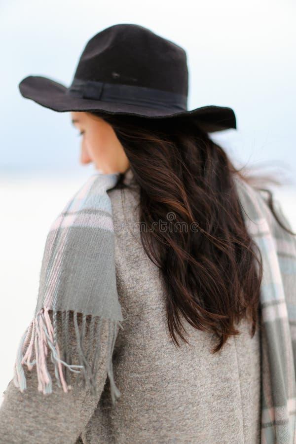Chapeau de port de jeune femme et manteau gris avec l'écharpe se tenant à l'arrière-plan blanc d'hiver images stock