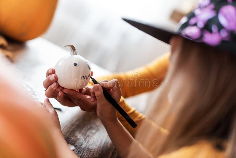 Chapeau de port de sorcière de jeune fille décorant le potiron blanc de Halloween, visage fantasmagorique de dessin Antécédents f photo libre de droits