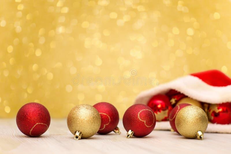 Chapeau de Santa Claus et rouge et boules d'or photos libres de droits