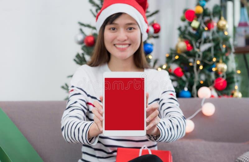 Chapeau de Santa d'usage de femme jugeant le comprimé se reposant sur le sofa avec le cadeau images stock
