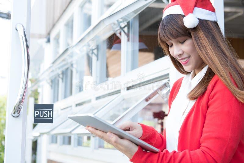 Chapeau de Santa d'usage de femme tenant le comprimé à sa boutique femelle asiatique nous photos stock