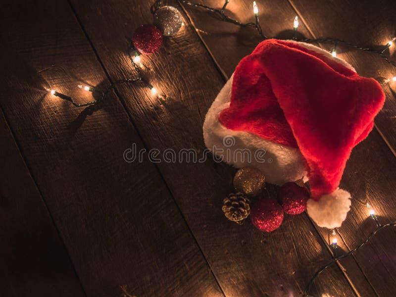 Chapeau de Santa et lumières de Noël sur le bureau en bois de vintage Fond de Noël photographie stock