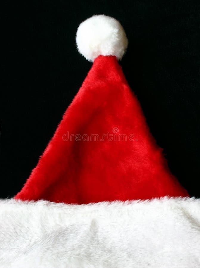 Chapeau de Santa s sur un fond noir photo libre de droits