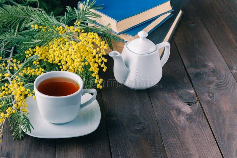 Chapeau de thé et livre sur le dessus de table images stock