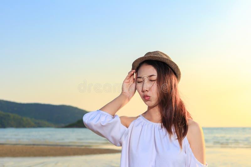 Chapeau de vêtements pour femmes de sourire de portrait et heureux sur la plage photo libre de droits