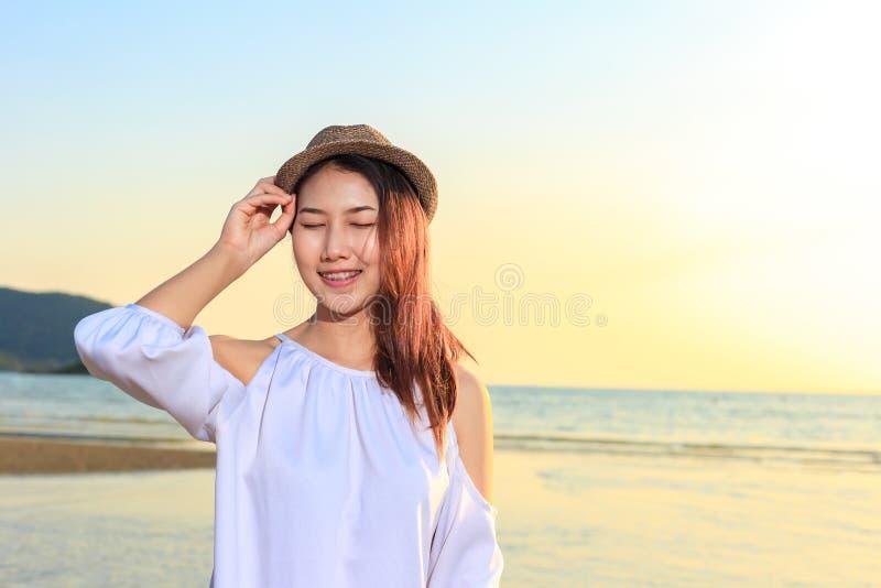 Chapeau de vêtements pour femmes de sourire de portrait et heureux sur la plage photographie stock libre de droits