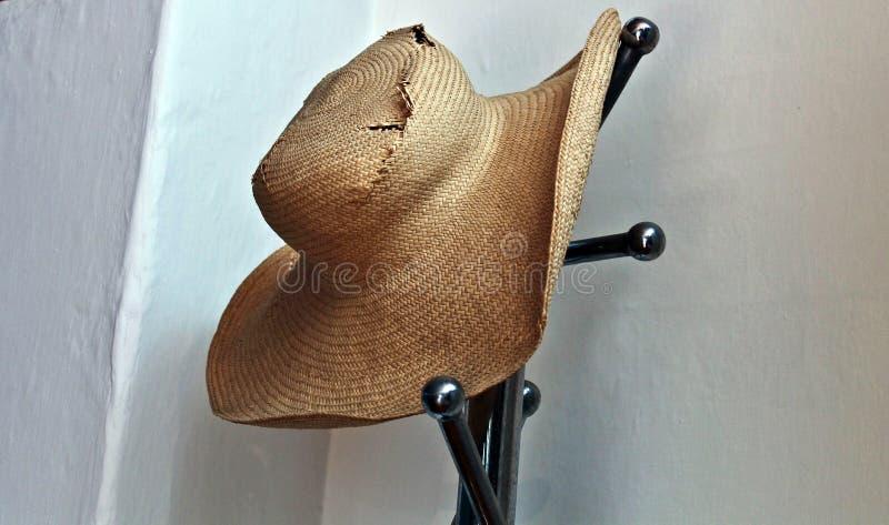 Chapeau de Wiker dans le cintre avec un mur blanc photographie stock