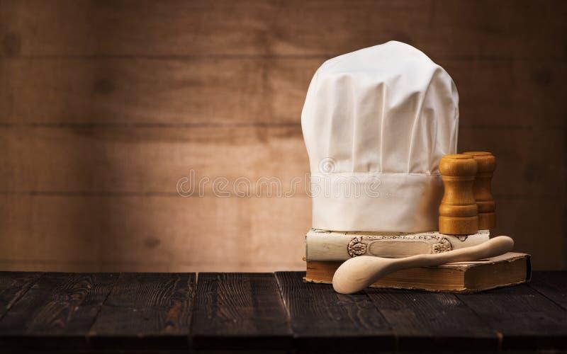 Chapeau du chef, livres de cuisine vintage et cuillère en bois sur la table de la cuisine avec espace pour le texte photographie stock