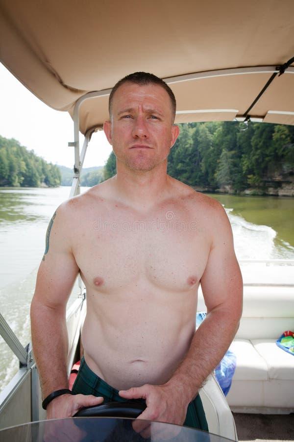 Chapeau en paille : Homme conduisant un bateau photo libre de droits