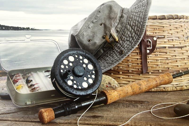 Chapeau et attirails de pêche de mouche sur la table près de l'eau image libre de droits