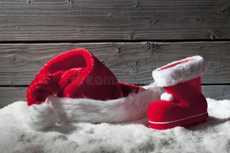 Chapeau et botte de Noël sur le tas de la neige sur le fond en bois image libre de droits
