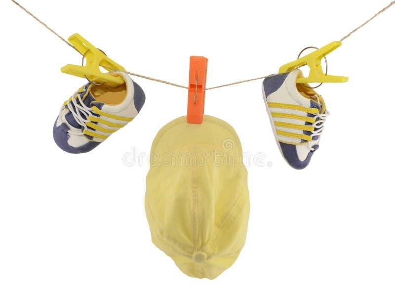 Chapeau et bottes de bébé sur la corde images stock