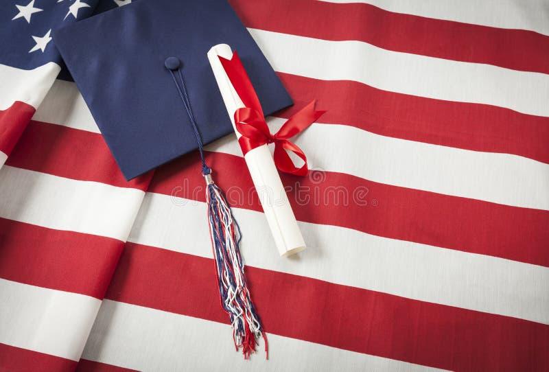 Chapeau et diplôme d'obtention du diplôme se reposant sur le drapeau américain images libres de droits
