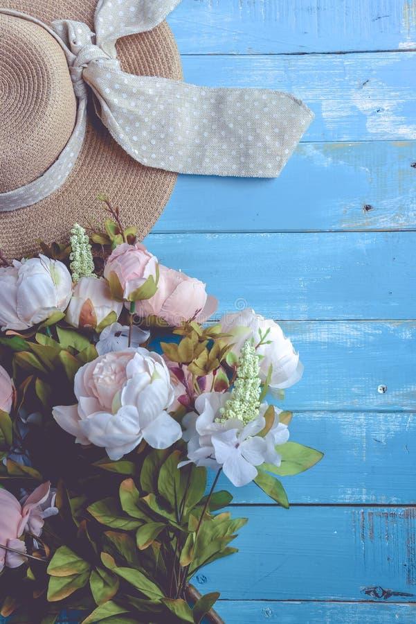 Chapeau et fleurs de Sun sur le fond en bois bleu de planche Les vacances et d?tendent le concept Ton en pastel image stock