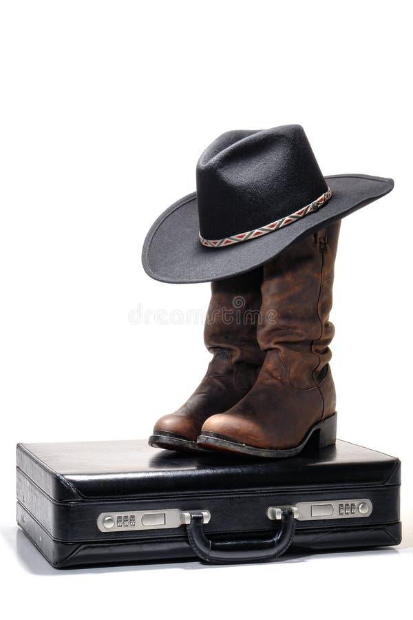 Chapeau et gaines de cowboy occidentaux sur la serviette d'affaires photos stock