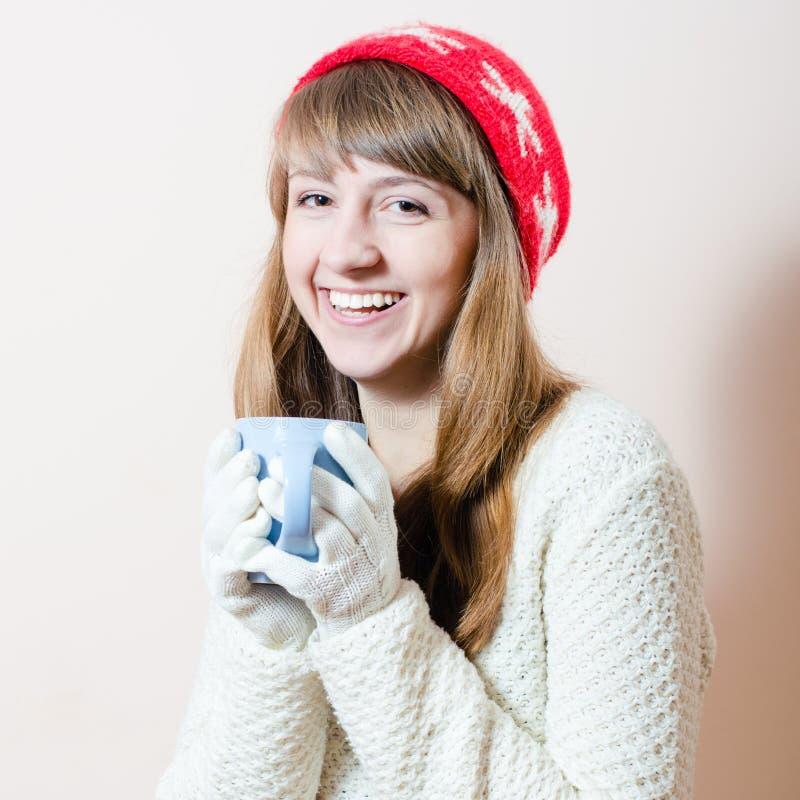 Chapeau et tasse rouges : portrait de jolie fille dans les gants tricotés et de chapeau avec des flocons de neige d'un modèle, ch photographie stock libre de droits