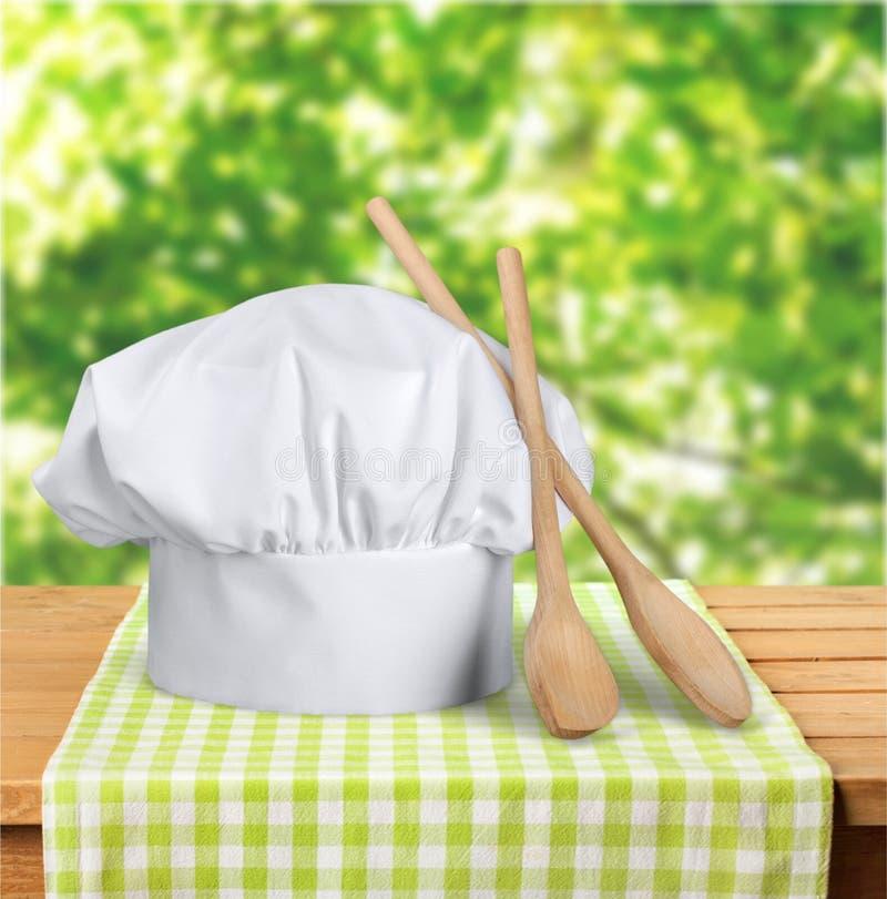 Chapeau et ustensiles blancs de chef sur la table photographie stock