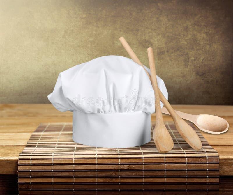 Chapeau et ustensiles blancs de chef sur la table image stock