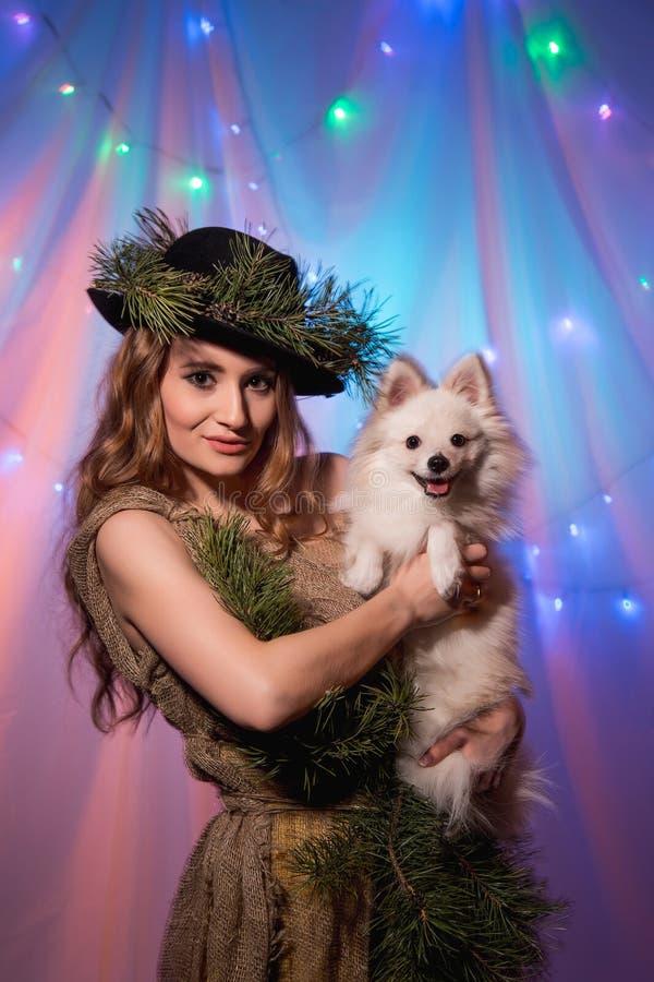 Chapeau féerique de belle forêt avec des branches de pin avec Pomeranian blanc photographie stock libre de droits