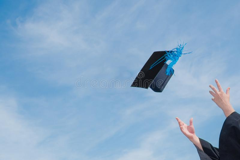 Chapeau licencié d'obtention du diplôme de jet de célébration de succès dans l'escroquerie de ciel photo libre de droits