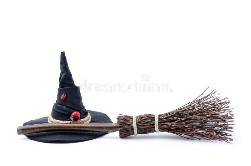 Chapeau magique de balai et de sorcière sur un fond blanc photographie stock libre de droits