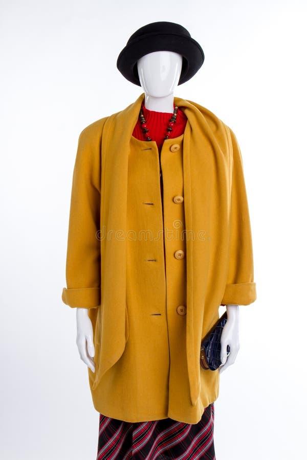 Chapeau noir et manteau jaune sur le mannequin photos libres de droits