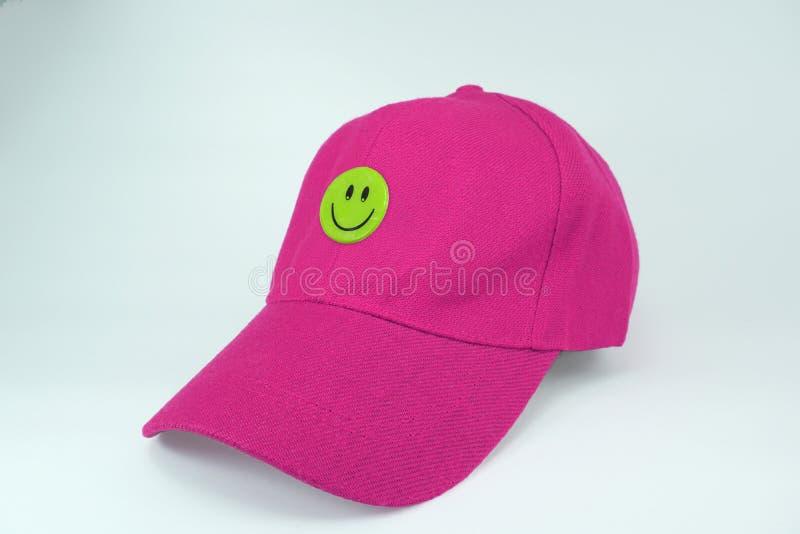 Chapeau rose avec le visage heureux souriant d'isolement sur le fond blanc photos stock